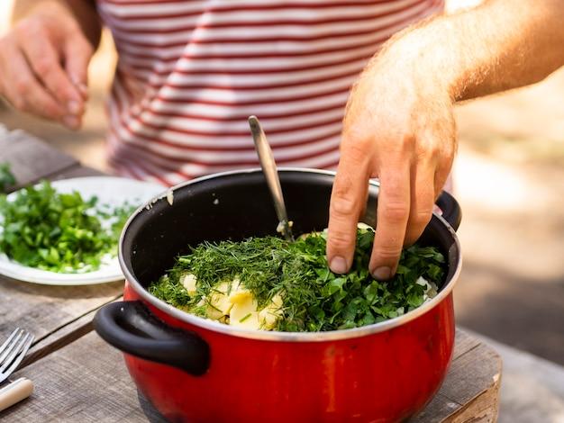 Onherkenbare kok die gekookte aardappels bestrooit met gehakte peterselie