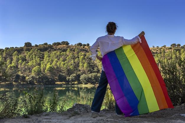 Onherkenbare lesbische vrouw van middelbare leeftijd die de gay rainbow flag vasthoudt aan het meer buitenshuis. vrijheidsconcept