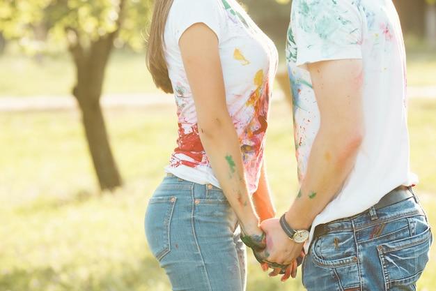 Onherkenbare man en vrouw die hun geschilderde kleurrijke t-shirts shawen op camera en glimlachen. mooie jongen en meisje plezier buitenshuis houden elkaar bij de handen