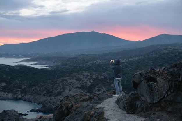 Onherkenbare man in hoodie staat bovenop wandelpad op berg