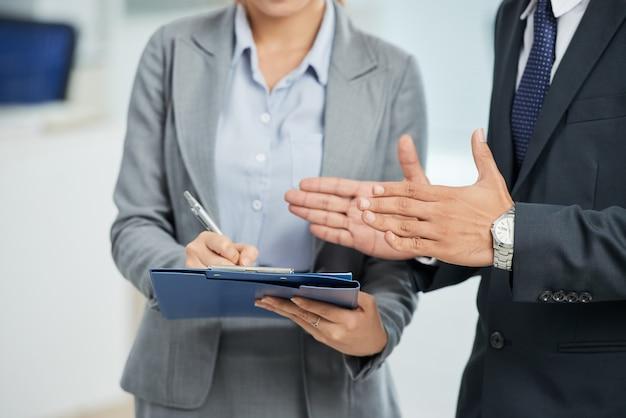 Onherkenbare man in pak gebaren en vrouw het maken van aantekeningen