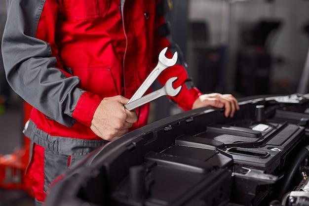 Onherkenbare man in uniforme moersleutels vasthouden en motor van het voertuig onderzoeken tijdens het werk in de garage