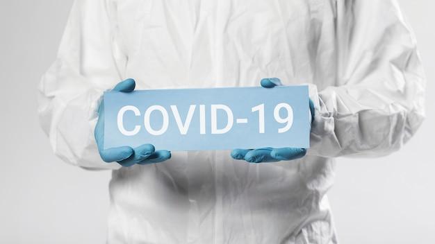 Onherkenbare man met covid-19-kaart