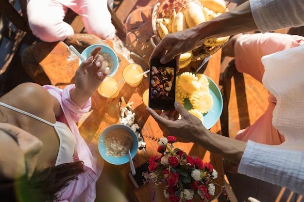 Onherkenbare man nemen foto van tafel geserveerd