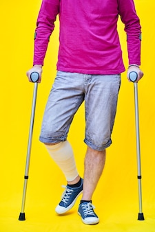 Onherkenbare man van voren met een paars hemd, korte broek en op krukken, met een verbonden been.