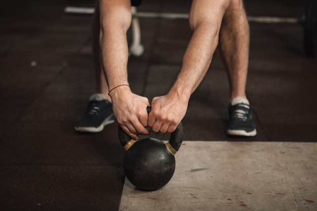 Onherkenbare mannelijke atleet die met kettlebell traint
