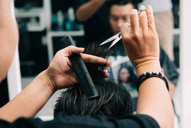 Onherkenbare mannelijke herenkapper die het haar van de klant voor spiegel snijdt