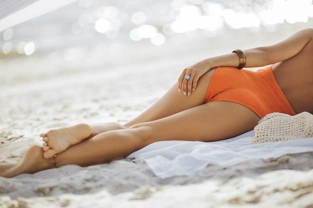 Onherkenbare mooie jonge vrouw in bikini die en op het strand achtermening ligt zonnen
