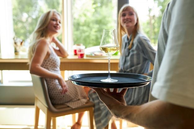 Onherkenbare ober in café bracht glazen champagne op dienblad naar jonge vrouwelijke klanten