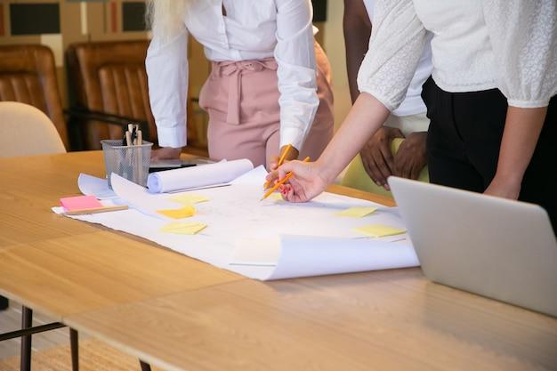 Onherkenbare ontwerpers die op een groot vel papier tekenen en ideeën uitwisselen