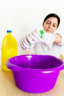 Onherkenbare schoonmaakster die een doekje met bleekwater leegmaakt om het huis te desinfecteren.