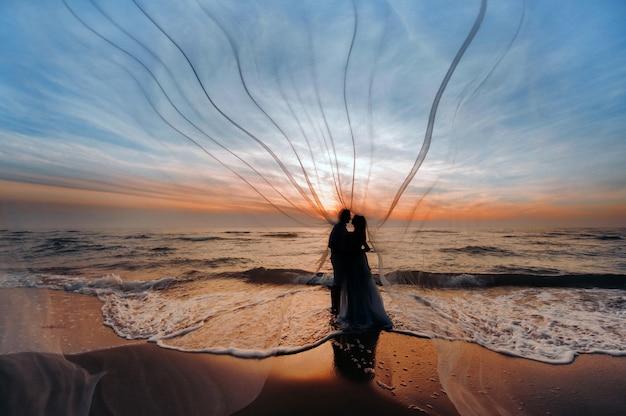 Onherkenbare silhouetten van een verliefd paar bij zonsondergang tegen de achtergrond van de zee, een onherkenbaar paarportret van een mooi pasgetrouwd stel dat een kind verwacht. foto,