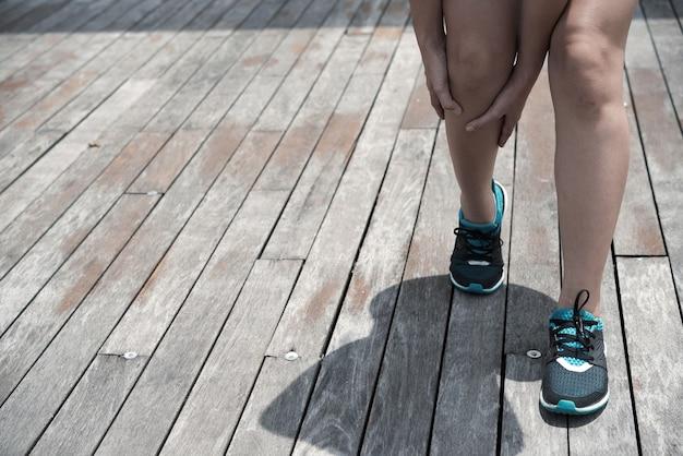 Onherkenbare sportvrouw in blauwe schoenen die een gespannen been aanraakt terwijl ze buiten op een houten oppervlak staat