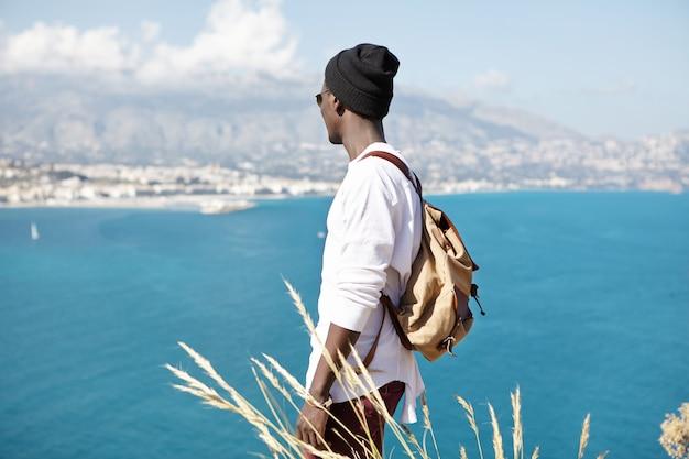Onherkenbare stijlvolle jonge afro-amerikaanse toerist die geniet van mooi zomerweer en een prachtig zeegezicht om hem heen terwijl hij bovenop de berg staat tijdens een excursie in een tropisch resort