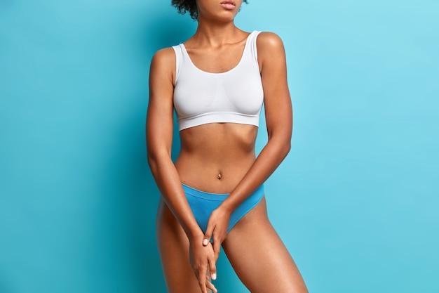 Onherkenbare superfit vrouw heeft een perfect slank lichaam, een platte buik houdt de handen tegen elkaar gedrukt, draagt een topje en een slipje poseert tegen een blauwe muur.