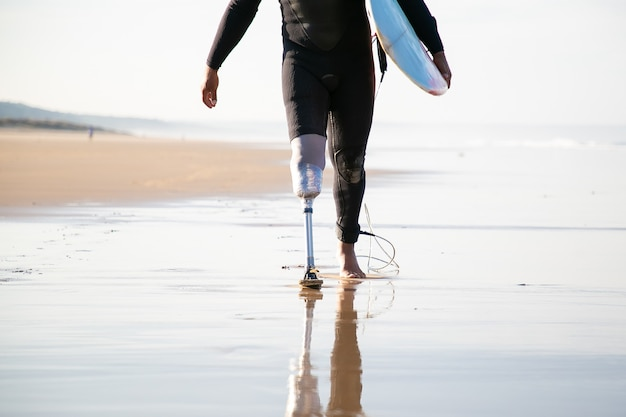 Onherkenbare surfer met beenprothese die in de buurt van zee loopt
