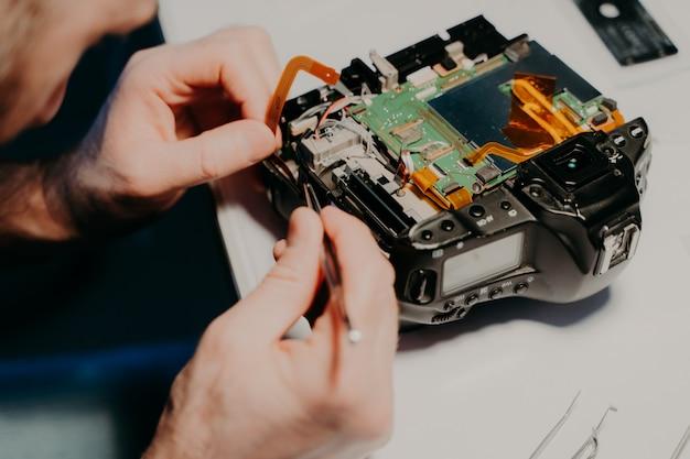 Onherkenbare technicus repareert gedemonteerde fotocamera, bezig op het werk, maakt gebruik van schroevendraaier.