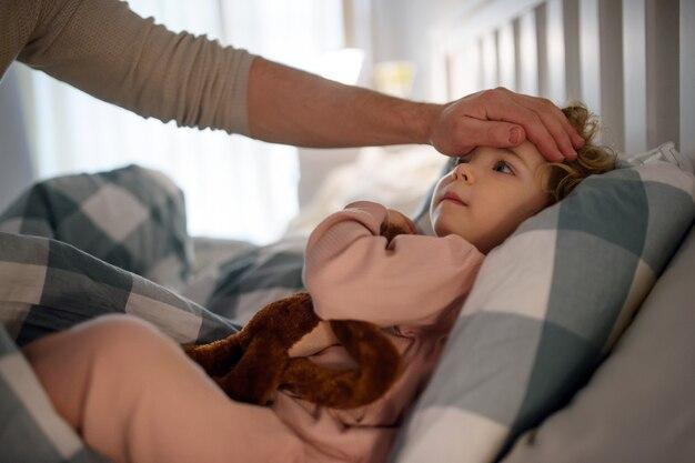 Onherkenbare vader die het voorhoofd van kleine zieke peuterdochter binnenshuis thuis controleert.