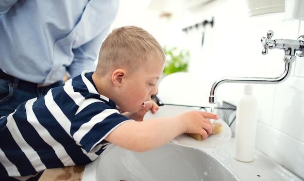 Onherkenbare vader met het syndroom van down zoon binnenshuis in de keuken, afwassen.