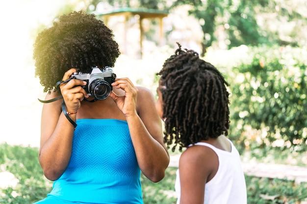 Onherkenbare volwassen vrouw met een analoge camera die een selfie maakt met een kleine jongen