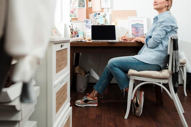 Onherkenbare vrouw die bij bureau werkt