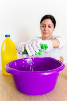 Onherkenbare vrouw die een afveegdoek met bleekwater leegmaakt om het huis te desinfecteren.