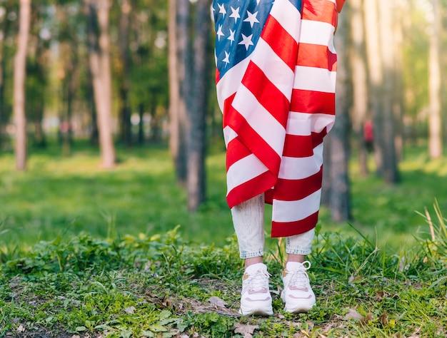 Onherkenbare vrouw die en zich in amerikaanse vlag in aard bevindt verpakken