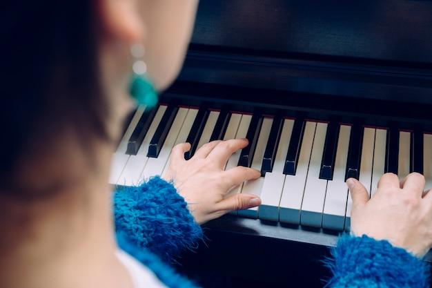 Onherkenbare vrouw die piano speelt. detail van vrouwelijke handen wat betreft een toetsenbord thuis. leraar pianist musicus die klassieke muziek repeteert. professionele muzikantenlevensstijlen binnenshuis.