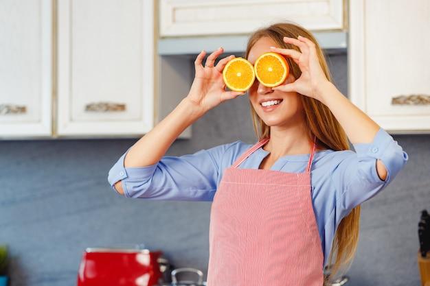 Onherkenbare vrouw die sinaasappels vasthoudt terwijl ze in de keuken staat