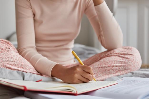Onherkenbare vrouw gekleed in casual nachtkleding, schrijft in notitieboekje, heeft inspiratie om te studeren.