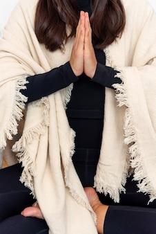Onherkenbare vrouw in activewear en sjaal mediteren in lotus houding met namaste handen tijdens yogasessie