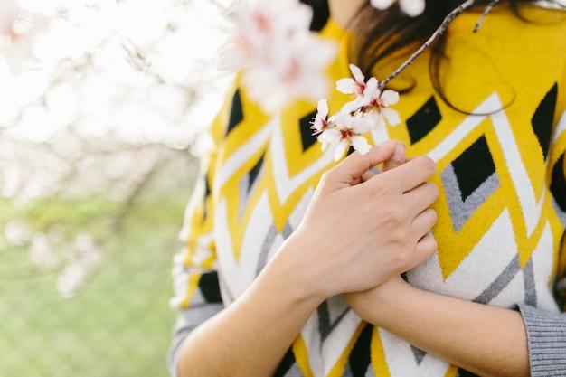 Onherkenbare vrouw in een gele trui met een tak van amandelbloesems met handen op de borst. geweldig begin van de lente. selectieve aandacht. vrouwelijkheid, feministisch en vrouwelijk concept.