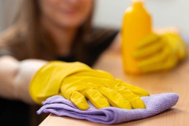 Onherkenbare vrouw in gele handschoenen die houten tafelblad close-up afvegen