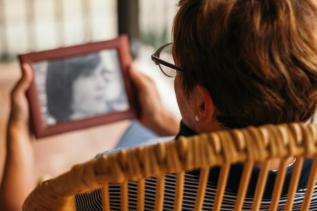 Onherkenbare vrouw kijkt een antieke foto toen ze jong was
