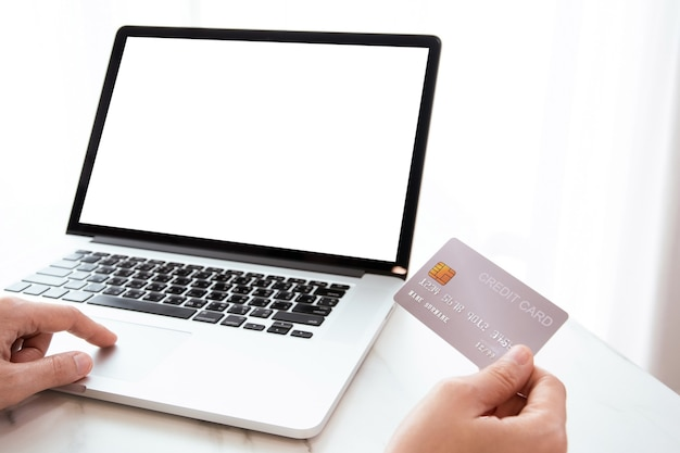 Onherkenbare vrouw met een creditcard voor het scherm van de laptopcomputer, online winkelen en veilig online betalingsconcept.