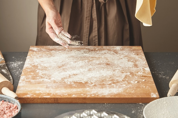 Onherkenbare vrouw voegt wat witte bloem toe aan een houten bord terwijl ze het deeg voor pasta of knoedels in de lucht plat houdt. ravioli koken stap voor stap gids
