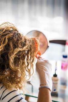 Onherkenbare vrouw werkt aan haar lange blonde haar met kleurstof om te kleuren