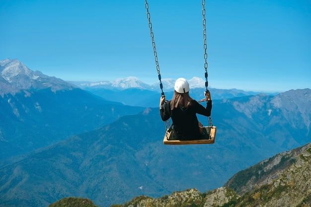 Onherkenbare vrouw zittend op een schommel in de bergen