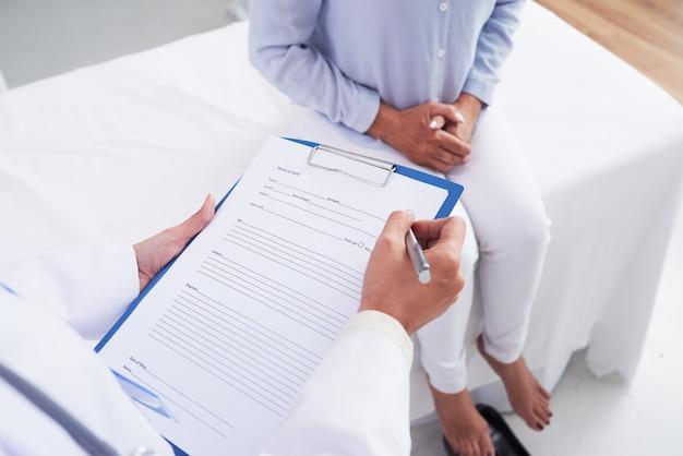 Onherkenbare vrouwelijke arts die document en geduldige zitting op laag invullen