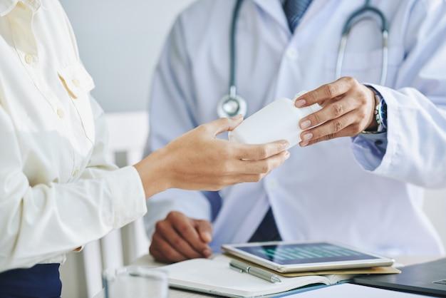 Onherkenbare vrouwelijke arts die medicijn geeft aan patiënt