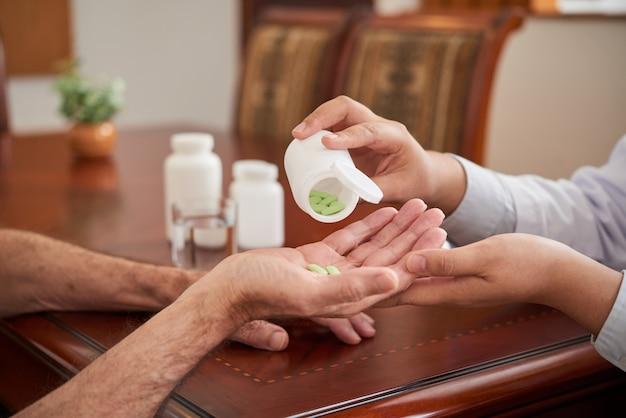 Onherkenbare vrouwelijke arts die pillen geeft aan mannelijke patiënt tijdens huisbezoek