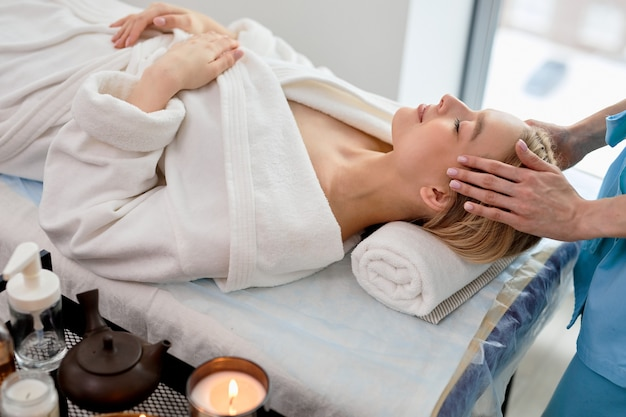 Onherkenbare vrouwelijke masseur in blauwe slijtage die ontspannende massage doet aan klantvrouw die op de bank ligt, blanke dame is ontspannen, genietend van spabehandeling in schoonheidssalon, in kamer met kaarsen