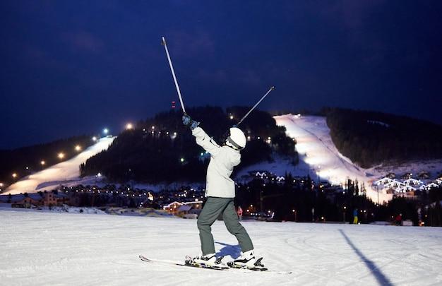 Onherkenbare vrouwelijke skiër met handen omhoog met skistokken