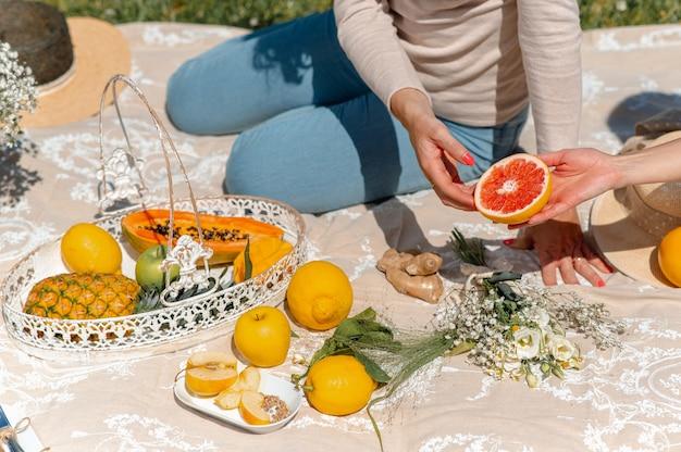 Onherkenbare vrouwen die op een deken zitten en picknicken. vrouwtjes passeren een roze grapefruit. verscheidenheid aan tropisch fruit rond.