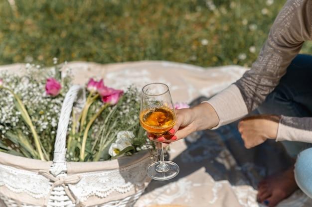 Onherkenbare vrouwenhand die een wijnglas met witte wijn houdt. mand met bloemen op picknickkleed