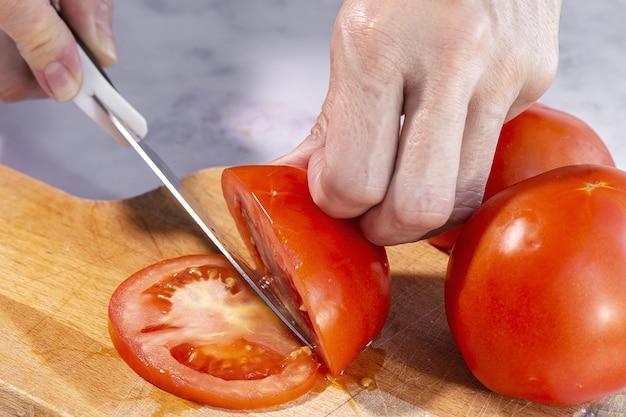 Onherkenbare vrouwenhanden die verse tomatenplakken snijden op een houten raad