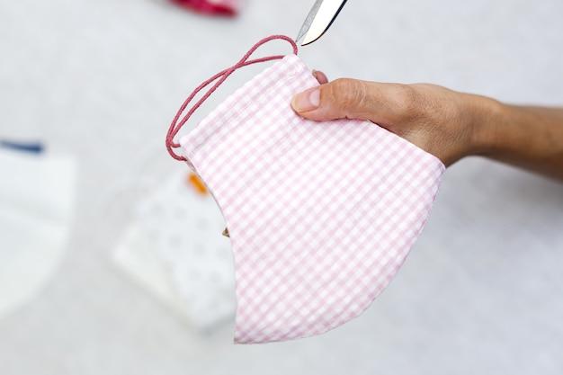 Onherkenbare vrouwenhanden met zelfgemaakte mode- en designmaskers voor covid-19-bescherming. coronavirus
