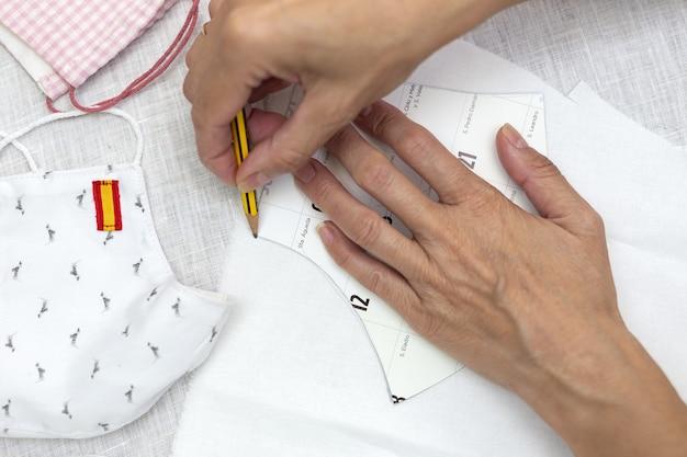 Onherkenbare vrouwenhanden snijden maskers op ter bescherming tegen de covid19 pandemie. coronavirus zelfgemaakt. schaar