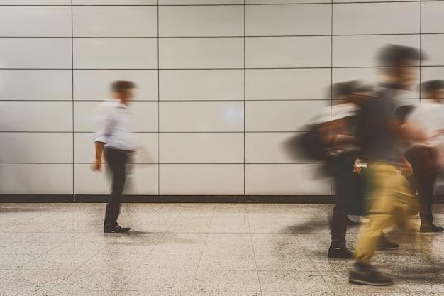 Onherkenbare werkende vrouw die en cellphone tussen bewegende vage motiereiziger in de hub van de vervoerskruising bevinden zich gebruiken