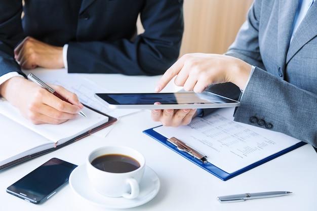Onherkenbare zakelijke collega's die samenwerken en een digitale tablet gebruiken
